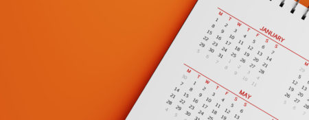 White calendar on orange background. January and may months are visible. Panoramic composition with copy space. Calendar and reminder concept with selective focus.